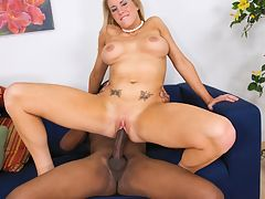A big boobed blonde slut riding a stiff black pecker